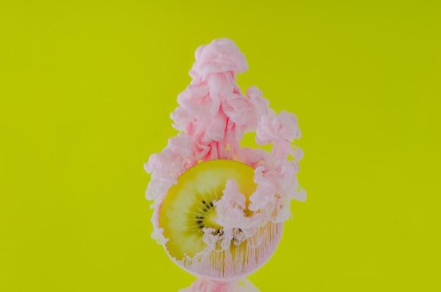 Snijd kiwi met gedeeltelijke focus van het oplossen van roze poster kleur in water