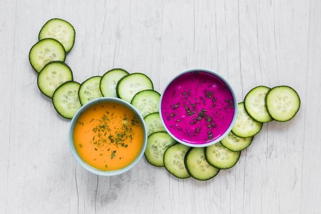 Snijd komkommer in de buurt van kommen met soepen