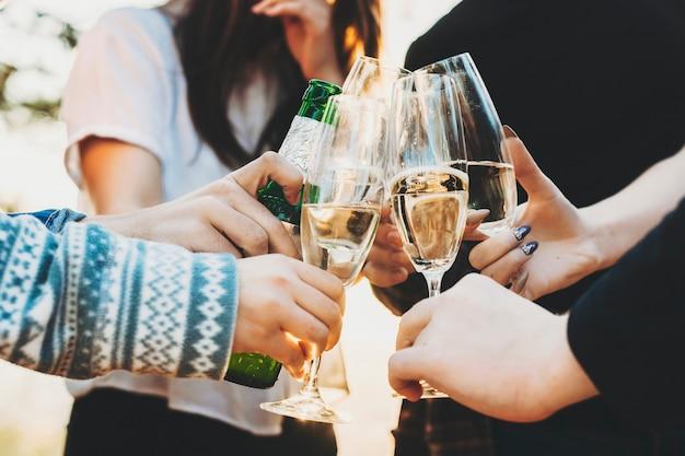 Snijd mensen rammelende glazen champagne en een fles bier bij terwijl ze vakantie vieren op een zonnige dag in de natuur