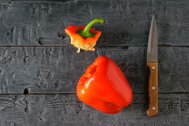 Snijd met een mes rijpe rode paprika op een zwarte tafel. vegetarisch eten. het uitzicht vanaf de top. plat leggen.