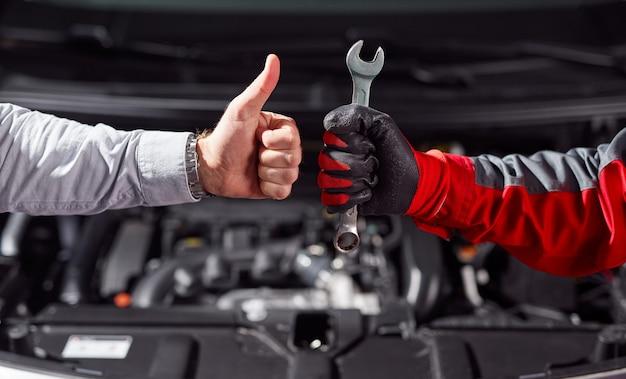 Snijd onherkenbare zakenman die duim omhoog gebaar toont terwijl hij met automonteur met in hand moersleutel in de buurt van kapotte auto in garage staat