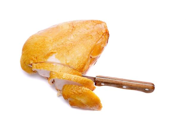 Snijd op gerookte kip met mes. geïsoleerd over wit.
