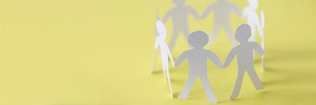 Snijd papieren mensen die een vakbondscirkel vormen op een gele achtergrond