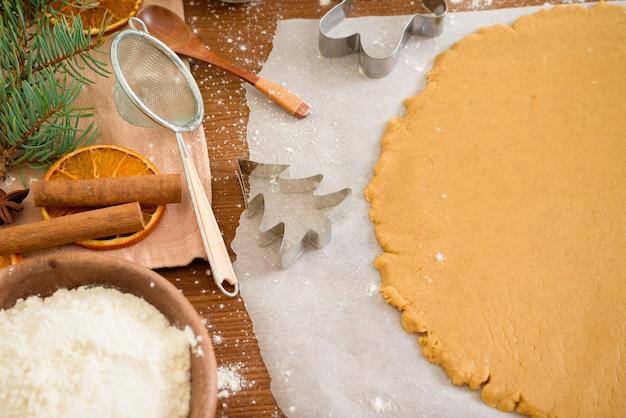 Snijd peperkoek uit het deeg met behulp van een peperkoekvorm, bovenaanzicht, deegroller, kaneel en vervolgens gedroogde sinaasappel.