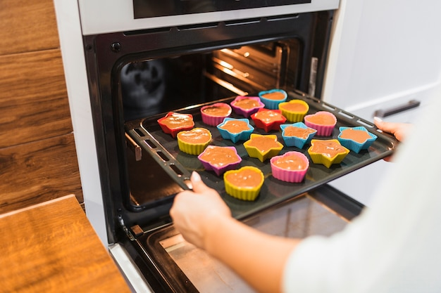 Snijd persoon die cupcakes bakken