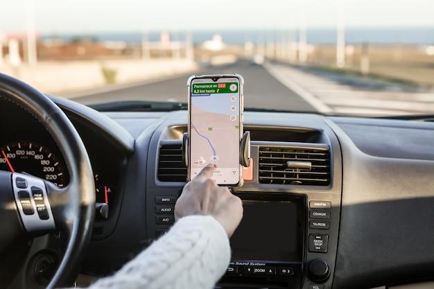 Snijd persoon die op de gps-kaart bladert op mobiele telefoon tijdens het autorijden tijdens een roadtrip