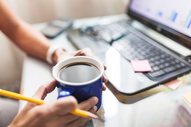 Snijd persoon het drinken van koffie in het kantoor
