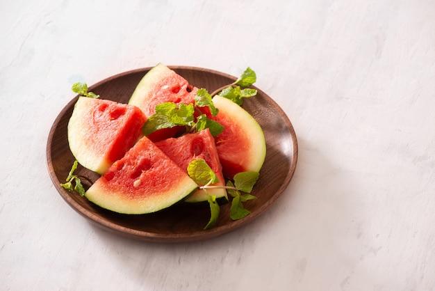 Snijd plakjes rijpe sappige watermeloen op houten plaat