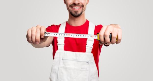 Snijd professionele werker bij in het algemeen demonstreren van meetlint en lachend vriendelijk terwijl je bouwgereedschap en service vertegenwoordigt