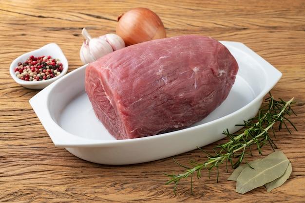 Snijd rauw oog rond vlees over witte plaat met kruiden.
