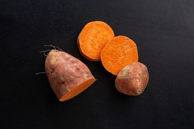 Snijd rauwe zoete aardappel op een donkere achtergrond. mockup. detailopname