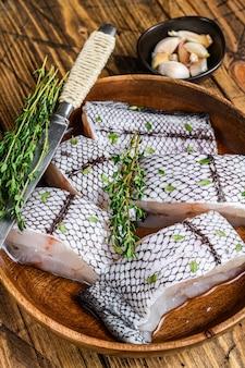 Snijd raw grenadier macrurus witvis zonder kop in een houten plaat. houten tafel. bovenaanzicht.