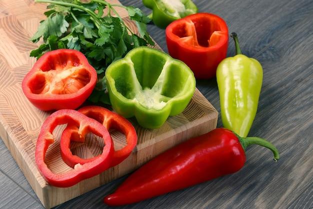 Snijd rode en groene paprika op houten ondergrond. gezonde verse groenten en eten