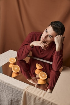 Snijd sinaasappels op een spiegel en een man aan een tafel op een bovenaanzicht van een stoffen achtergrond. hoge kwaliteit foto