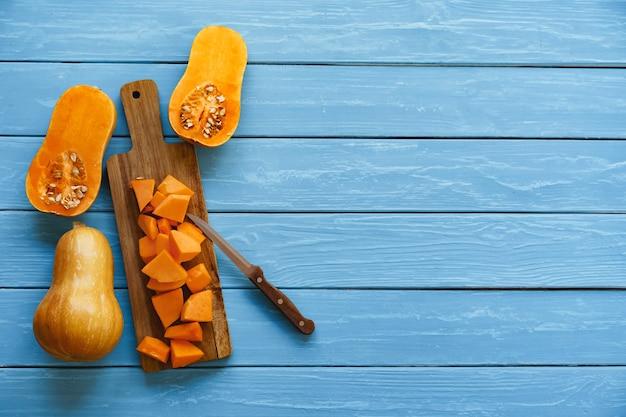 Snijd stukjes rauwe pompoen op een houten snijplank op tafel