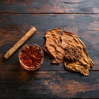 Snijd tabak en tabaksbladeren met sigaar en whisky-rum op hout
