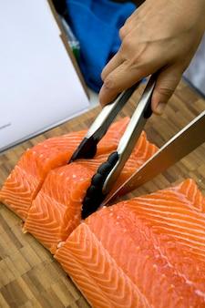 Snijd verse zalm in voorbereiding voor het koken