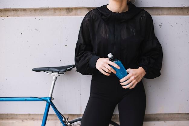 Snijd vrouw met fles dichtbij fiets