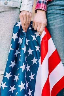 Snijd vrouwelijke handen met de kleurrijke vlag van de vs
