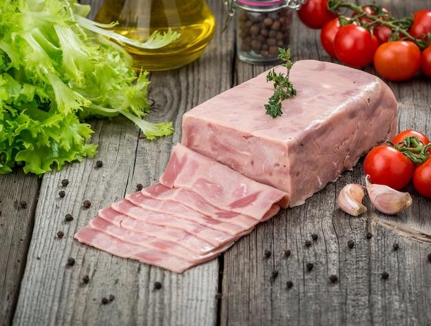Snijd worst van ham op een houten achtergrond