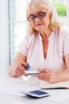 Snijden in haar budget. geconcentreerde oudere vrouw die haar creditcard met een schaar knipt terwijl ze aan tafel zit
