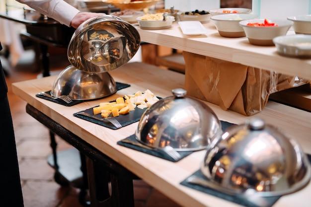 Snijden kaas op een metalen kom met een dop. ontbijt in het hotel of restaurant.