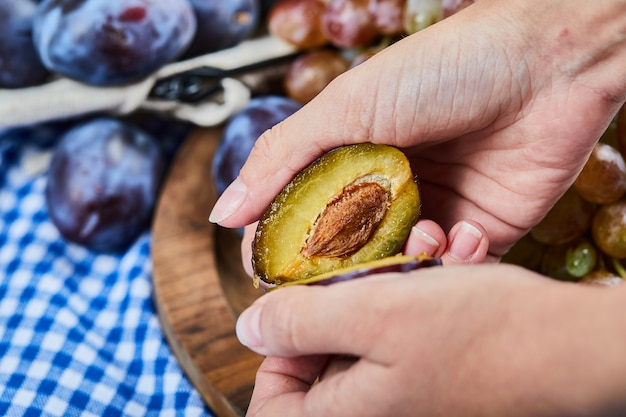 Snijden pruim met een tros druiven en pruimen op houten plaat.