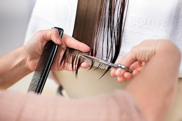 Snijden uiteinden van lang bruin haar in close-up