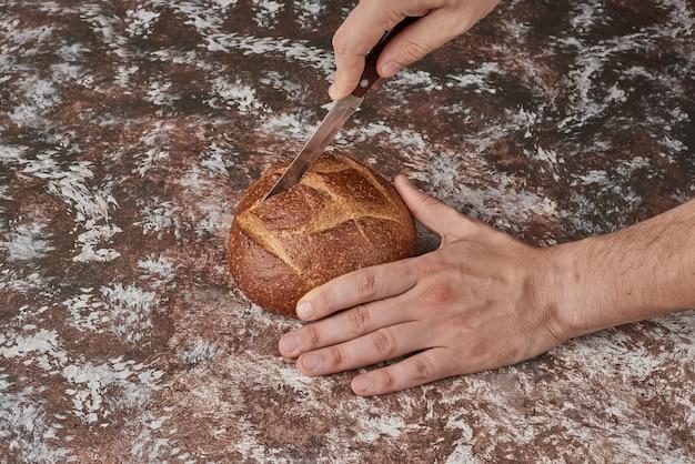 Snijden van brood op de marmeren achtergrond