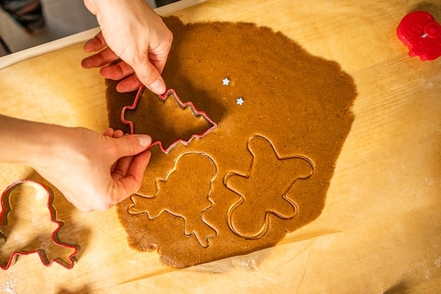Snijden van peperkoekvormen. een jonge vrouw snijdt peperkoekvormen op bruna-bakpapier. rode peperkoekvormen.