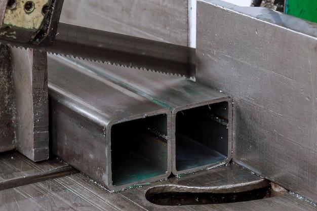 Snijden van stalen profielen en buizen op een lintzaag in productie.