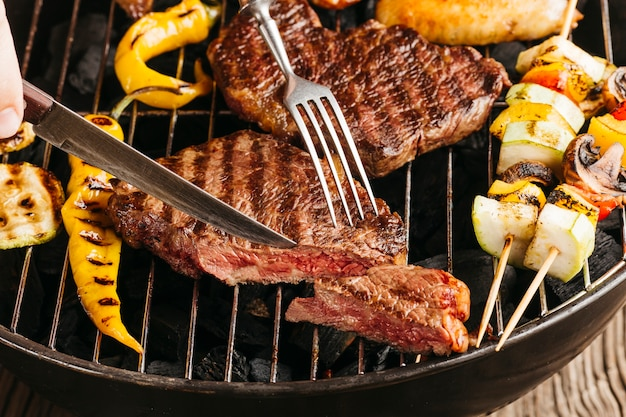 Snijdende de biefstukplak van de hand met botermes en vork op barbecuegrill