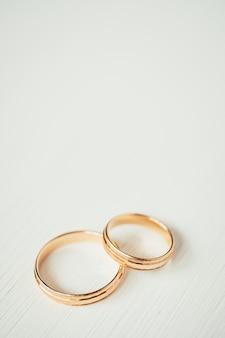 Snijdende huwelijks gouden ringen bij de bodem van de witte houten achtergrond