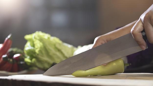 Snijdende spaanse peper met keukenmes op houten raad, sluit omhoog