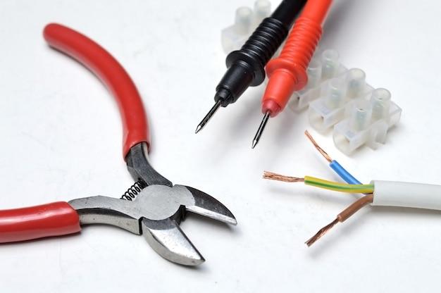 Snijders, elektrische draad, meetprobes en klemmenblok close-up.