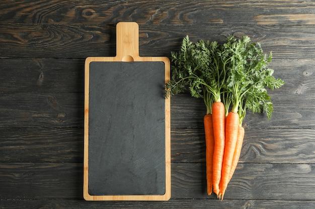 Snijplank en rijpe wortelen op houten tafel