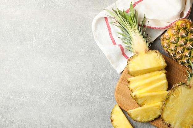 Snijplank met ananas op grijze achtergrond, bovenaanzicht