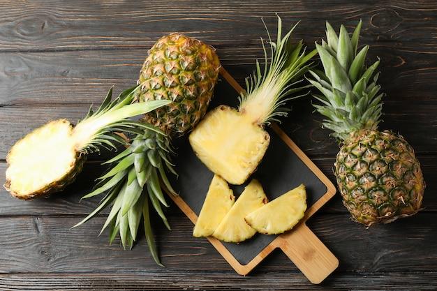 Snijplank met ananas op houten achtergrond, bovenaanzicht