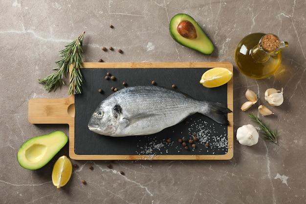 Snijplank met dorado vis en koken ingrediënten op grijze achtergrond, bovenaanzicht