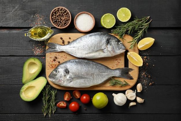 Snijplank met dorado-vissen en kokende ingrediënten op houten achtergrond