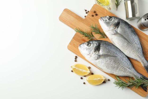 Snijplank met dorado-vissen en kokende ingrediënten op witte achtergrond, hoogste mening