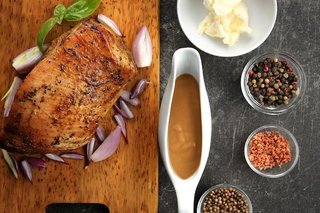 Snijplank met heerlijke kalkoen, kruiden en juskom op grijze tafel