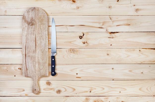 Snijplank met mes op houten tafel. bovenaanzicht