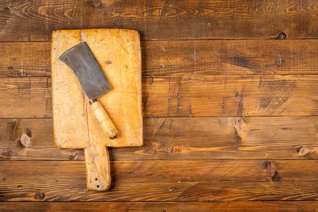 Snijplank met oude keukenmessen in houten tafel