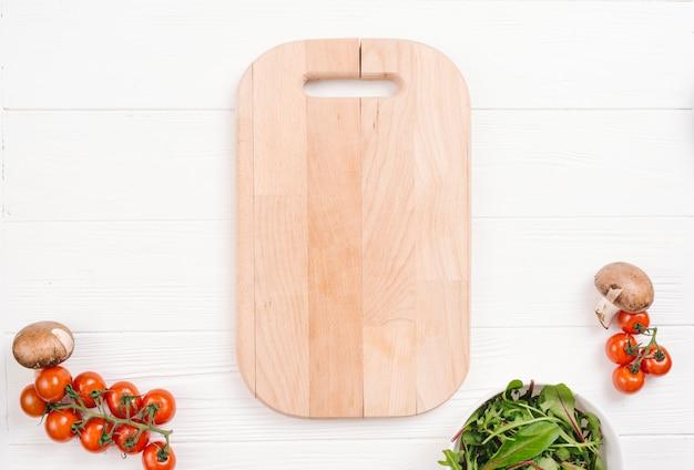 Snijplank met paddestoel; cherry tomaten en zwitserse snijbiet op witte houten tafel