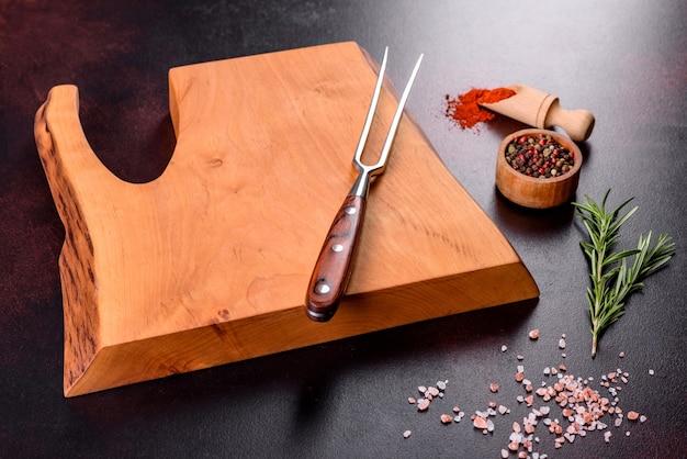 Snijplank met zout, specerijen en kruiden op een donkere betonnen achtergrond. gezond eten koken