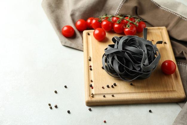 Snijplank met zwarte ongekookte pasta