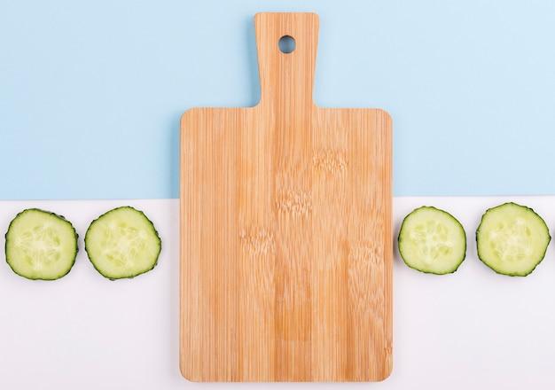 Snijplank omgeven door plakjes komkommer