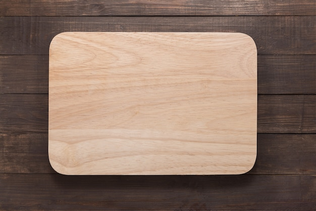 Snijplank op de houten achtergrond. bovenaanzicht