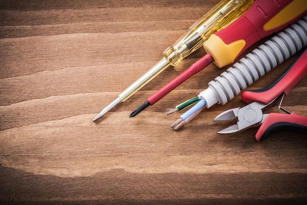 Snijtang geïsoleerde schroevendraaiers gegolfd pijp op houten bord.